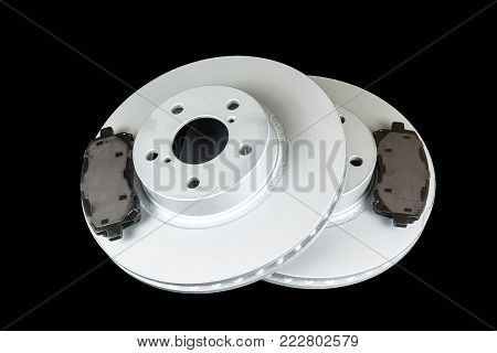 Brake discs and pads on a black background