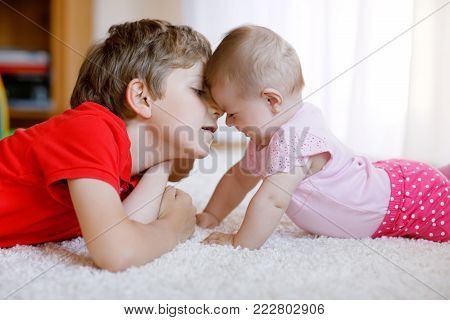 Happy little kid boy with newborn baby girl, cute sister. Siblings. Brother and baby playing together. Older child showing baby crawling. Family and love.