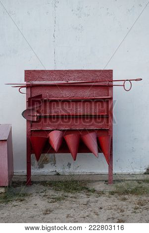 Red old fire shield against the white wall, screech, scrap, five fire cone buckets, two shovels - bayonet and shovel, extinguishing of burning fuels and gases, fire, 911
