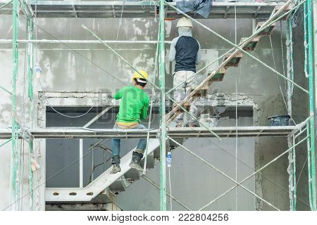 Construction workers working on scaffolding, Man Working on the Working at height with safety belt at construction site