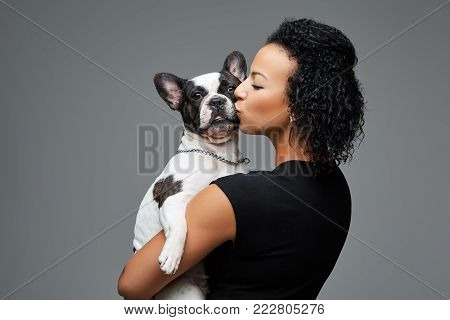 beautiful young woman holding french bulldog dog. studio shot over grey background. copy space.