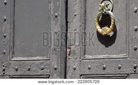 Ancient golden handle knob on Wooden Door. Metal carving door knocker. An Asian traditional photo.