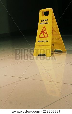 Save Download Preview Sign showing warning of caution wet floor on the wet tile floor. The hotel