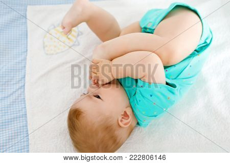 Cute baby taking feet in mouth. Adorable little baby girl sucking own foot.