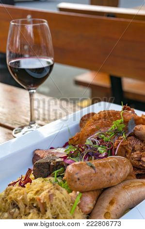 German sausages with meat, vegetables and sauerkraut, cabbage with glass of red wine on the background. Al fresco restaurant dinning food background