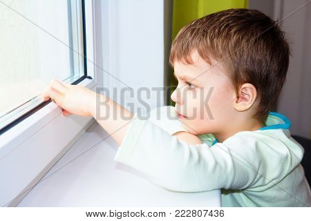 sad little boy looks out the window. Portrait of Caucasian boy near window. Melancholic child