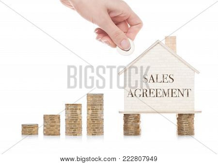 Wooden house model standing on coins and hand holding the coin with conceptual text.  Sales Agreement
