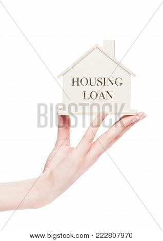 Female hand holding wooden house model with conceptual text. housing Loan