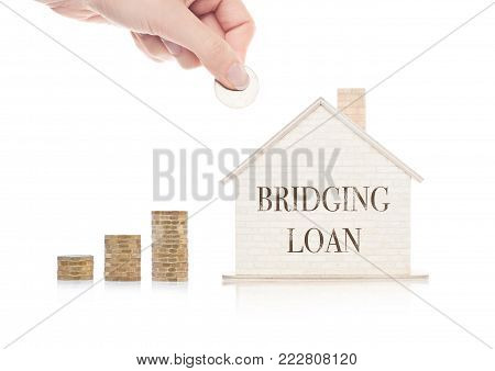 Wooden house model with coins next to it and hand holding the coin with conceptual text. Bridging loan
