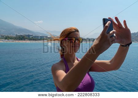 Attractive young girl taking a selfie portrait with cell phone on the boat, smiling. Filmed against the backdrop of the Mediterranean sea and the coast with beaches