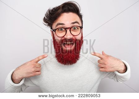 Excited stylish man pointing at his beard in red glitter looking excitedly at camera.