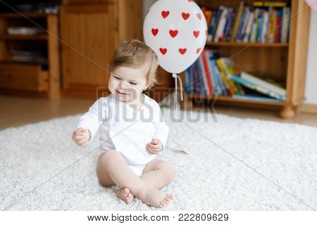 Adorable cute beautiful little baby girl playing with educational toys at home or nursery. Happy healthy child having fun with colorful different toys. Toddler learning different skills