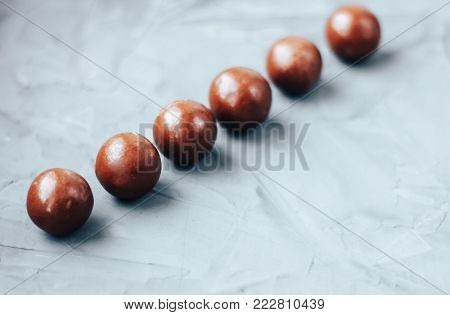 a line of Chocolate-coated candy bon bon, chocolate balls on concrete table, space for text