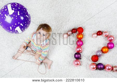 Adorable baby girl holding colorful vintage xmas toy ball in cute hands. Little child and Christmas tree balls as twelve. Toddler celebrating Xmas and first birthday