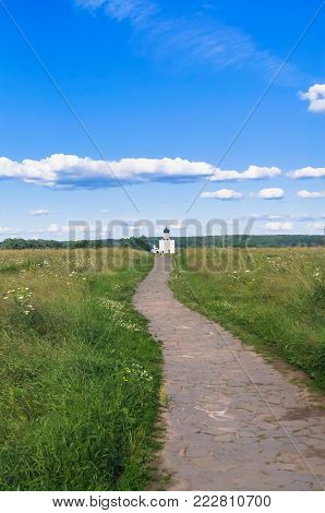The stone-paved trail through the Bogolubovo meadow towards the ancient orthodox Church of the Intercession on the Nerl River. Russia.