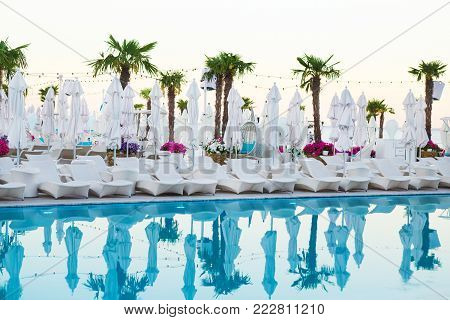 Swimming pool with palm tree, white umbrella and chaise-longue. Hotel resort pool on sunset time. Reflections of palms in the pool