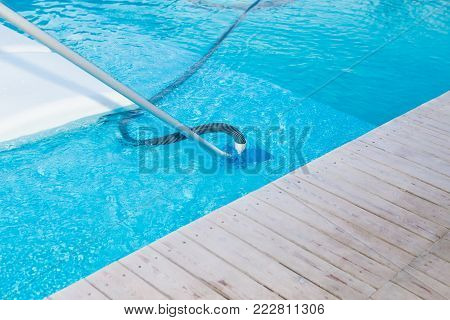 Swimming pool vacuum cleaner close up view. Pool cleaning process. Pool maintenance. Pool cleaner machine