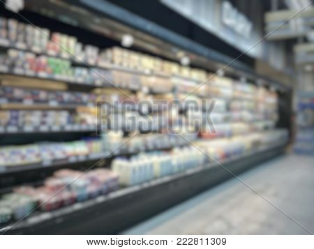 Supermarket place blur background with dairy food products and beverage on blurry refrigerator shelves