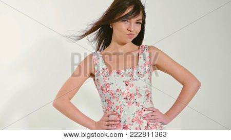 Funny portrait of pretty teen girl is thinking and showing disagree emotions at white studio background
