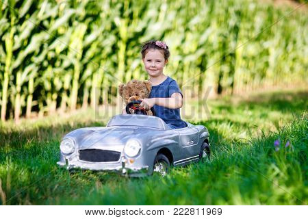 Happy little kid girl driving big vintage old toy car and having fun with playing with big plush toy bear, outdoors. Child enjoying warm summer day in nature landscape. Girl driving car.