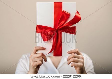 A woman in a white shirt holds a white gift box with a red satin bow and hides her head behind a box, cropped image