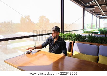 American handsome businessman speaking with partner by smartphone and charging with power bank. Attractive man has beard and dark hair, wears watch and black shirt. Concept of biz talks, good mobile tariff plan and modern gadgets.