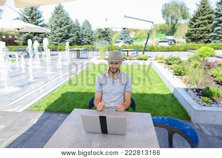 Skilled actuary working with laptop and documents at cafe table. Handsome man dressed in white shirt sitting near green plants on sofa and typing with keyboard. Concept of a person compiling and analyzing statistics, using to calculate insurance risks