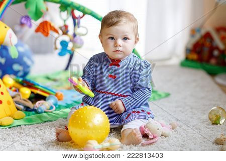 Adorable baby girl playing with educational toys in nursery. Happy cute healthy child having fun with colorful different toys. Toddler learning different skills like throwing catching ball