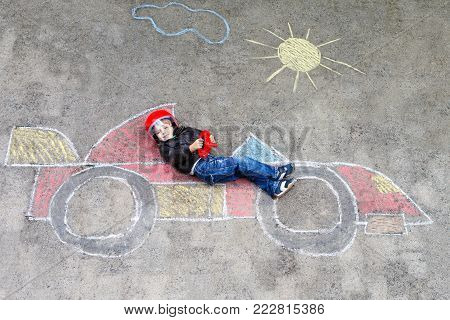 Adorable little kid boy drawing with colorful chalks race car picture on asphalt. Cute toddler and preschool child playing racing driver. Creative leisure with small kids outdoors