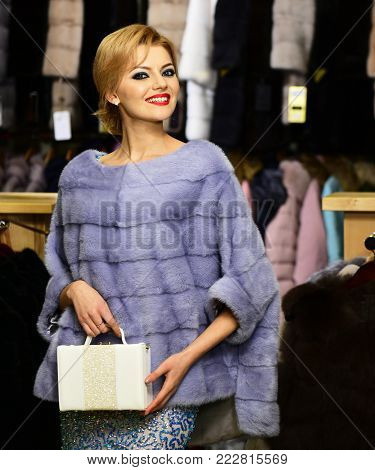 Girl with happy face wears furry coat on clothes rack background. Elegance and glamour concept. Lady with white purse tries expensive grey mink overcoat on. Woman with blond hair buys furry coat.