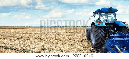 Tractor working on the farm, a modern agricultural transport, cultivation of fertile land, tractor on cloudy sky background, agricultural machine