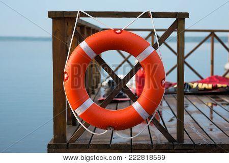 Marine Lifebuoy On Fence, On Water Background.