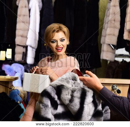 Girl In Pink Fur Looks At Coat In Male Hands.