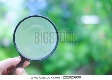 Hand holding a magnifying glass on blurred natural green background, added colour fitter and soft tone poster