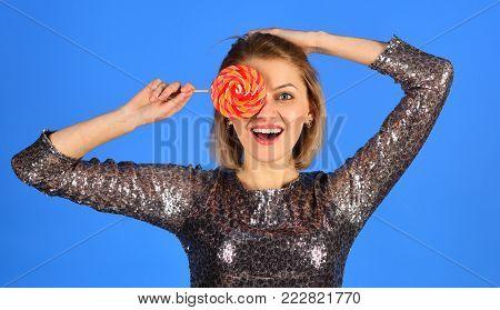 Woman Holds Lollipop Hiding Eye On Blue Background.
