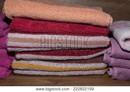 Many colorful towels stacked in the closet