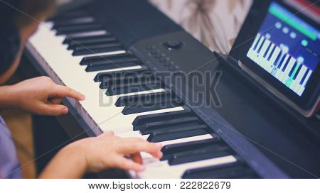 The Boy Learns To Play Piano Using Application For Digital Tablet. Keyboard Piano. The Boy Sits At T