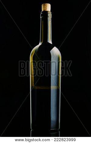 Open Bottle Of Red Wine. Half A Bottle Of Wine. A Bottle Of Wine On A Black Background. Bottle With