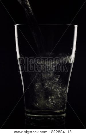 Glass Glass In Which Water Flows On A Black Background. The Water Is Clean - The Glass Is Transparen