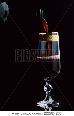 Red Wine Being Poured Into A Glass On A Black Background