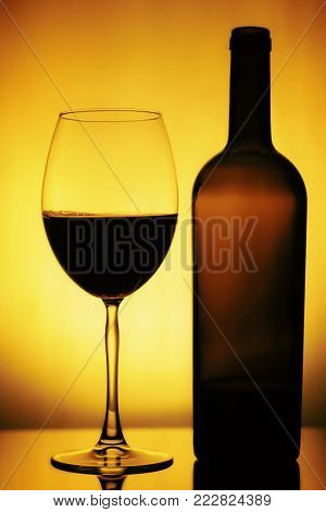 Glass And A Bottle Of Wine. Bottle Is Open, Half Of It Is Wine. Glass And Bottle Of Wine On A Yellow