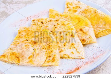Indian naan bread with spices on white plate