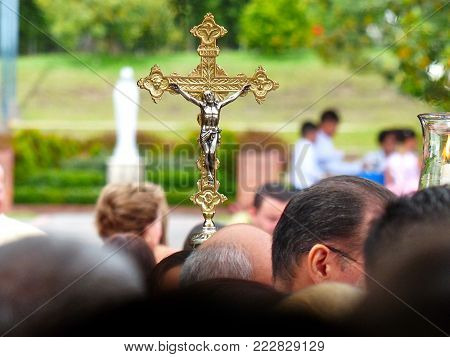 golden holy cross above the heads of people with blurred background