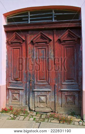 Old and discolored red door in Slavonia, Croatia