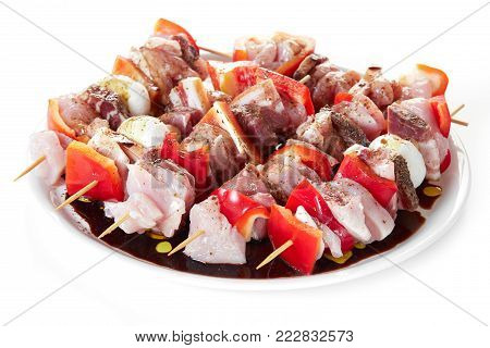Skewers with pieces of raw meat, red pepper, bacon and mushrooms, seasoned with coarse salt, olive oil and balsamic vinegar, plate isolated on white background.