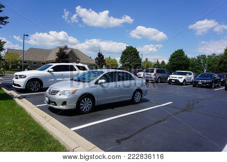 JOLIET, ILLINOIS / UNITED STATES - JULY 30, 2017: Automobiles are parked in the parking lot of the Wesmere Country Club Clubhouse.