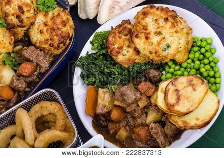 Beef in Irish Stout Stew with Dumplings A dish of Beef in Irish stout with a topping of cheese and spring onion Dumplings, served with a selection of vegetables and Sourdough bread, with stout battered onion rings and a jug of onion gravy.