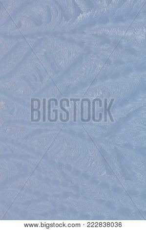 Bright blue frost pattern on a window glass in the winter as an abstract winter background, retro style