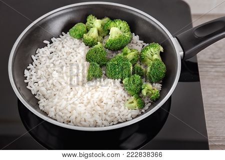 Frying pan with rice and broccoli on electric cooker