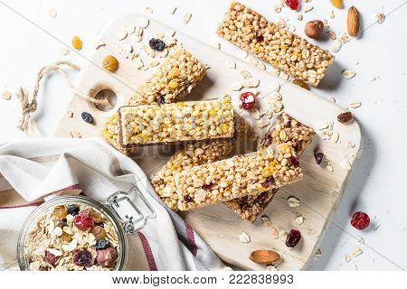 Granola bar with nuts, fruit and berries on a white stone table. Healthy sweet dessert snack. Top view.